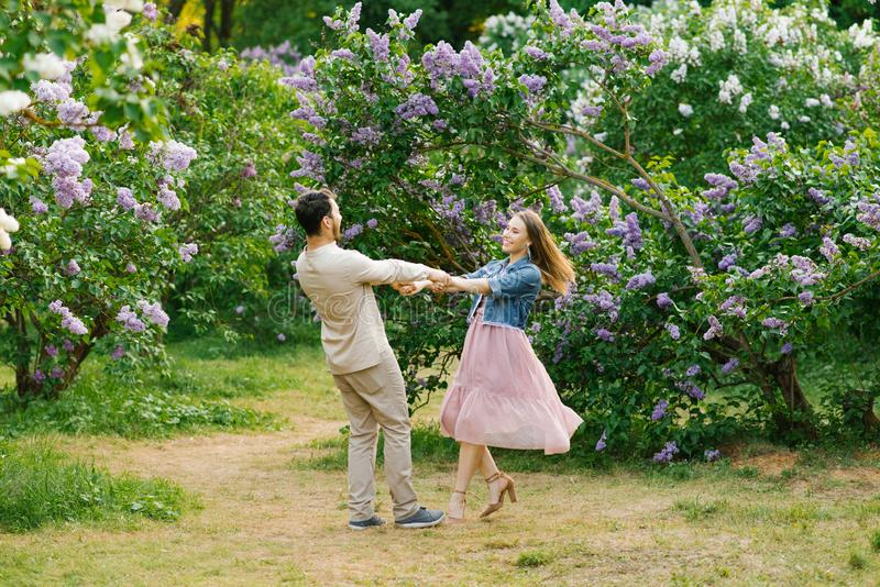 De jonge het houden van handen van de paarholding en het spinnen in de lilac tuin royalty-vrije stock foto