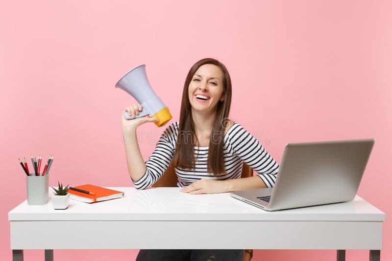 De jonge het lachen megafoon van de vrouwenholding terwijl het zitten en het werken aan project bij wit bureau op kantoor met PC- royalty-vrije stock fotografie
