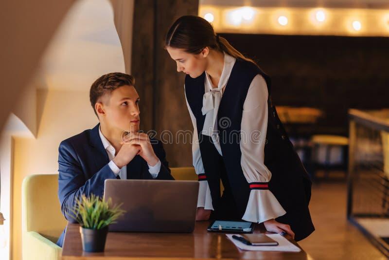 De jonge het zakenliedenjongen en meisje werken met laptop, een tablet en nota's in de koffie stock fotografie