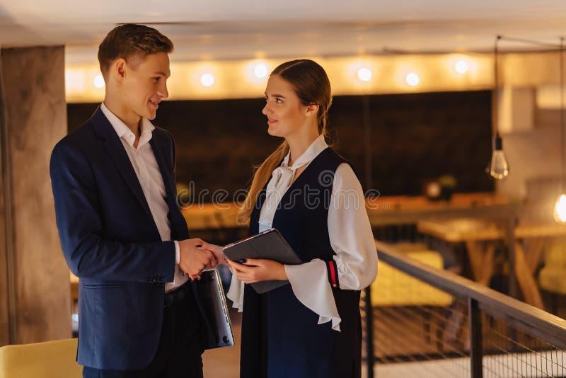 De jonge het zakenliedenkerel en meisje in een comfortabel binnenland zijn akkoord gegaan, zaken en freelance royalty-vrije stock afbeelding