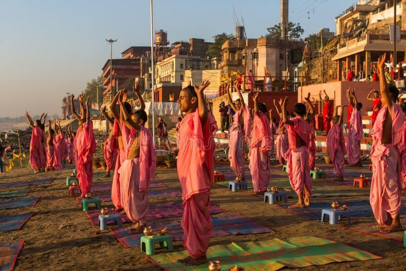 De jonge Hindoese monniken leiden een ceremonie om de dageraad op de banken van de Ganges te ontmoeten, en heffen de Indische vla royalty-vrije stock afbeeldingen