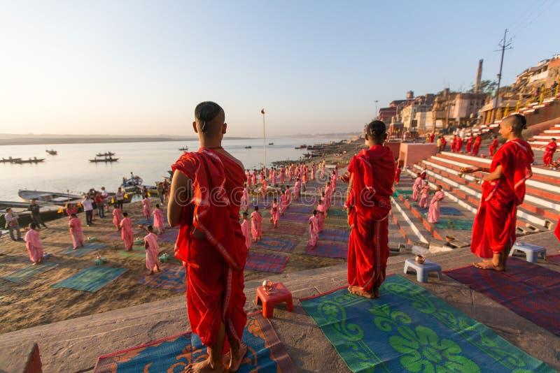 De jonge Hindoese monniken leiden een ceremonie om de dageraad op de banken van de Ganges te ontmoeten, en heffen de Indische vla stock foto's