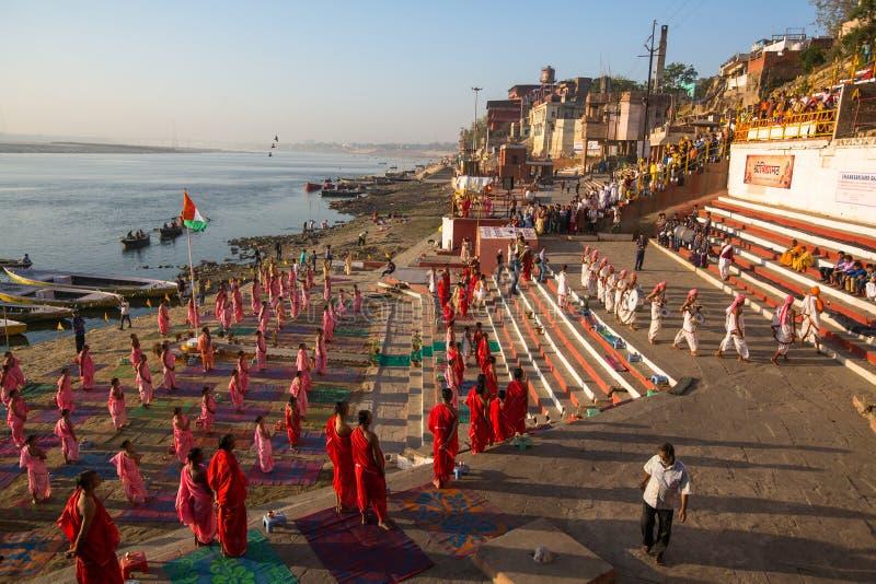 De jonge Hindoese monniken leiden een ceremonie om de dageraad op banken van Ganges te ontmoeten, en heffen de Indische vlag op royalty-vrije stock afbeelding