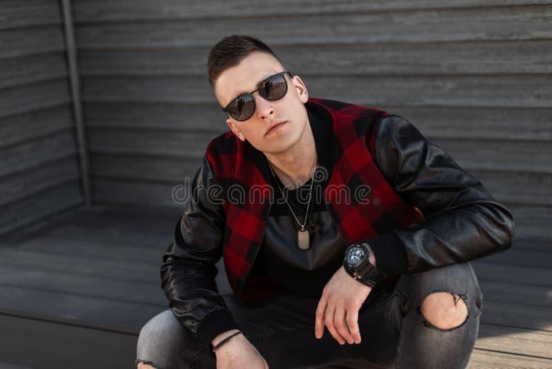 De jonge hipstermens in gescheurde grijze jeans in een in geruit jasje in modieuze zonnebril zit op uitstekende treden stock afbeeldingen