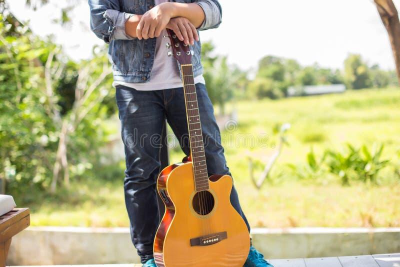 De jonge hipstermens oefende gitaar in het gelukkige park uit, en geniet van speel gitaar stock foto