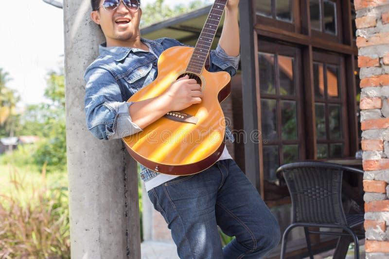 De jonge hipstermens oefende gitaar in het gelukkige park uit, en geniet van speel gitaar stock fotografie