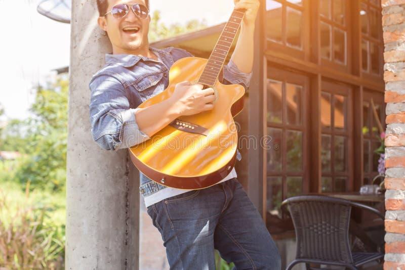 De jonge hipstermens oefende gitaar in het gelukkige park uit, en geniet van speel gitaar royalty-vrije stock fotografie