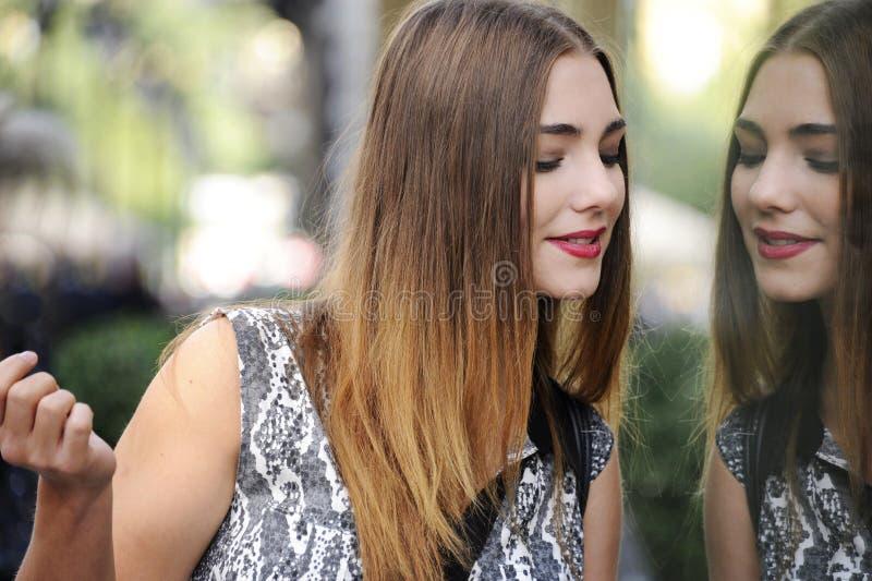 De in jonge hipstervrouw kijkt door winkelvenster, denkt haar gezicht na stock foto's