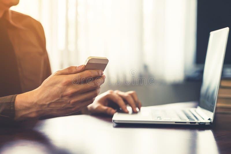 De jonge holding van de bedrijfsmensenhand en het gebruiken van smartphone in offi stock foto