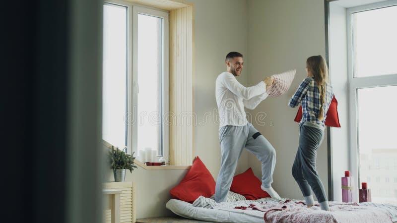 De jonge hoofdkussens van de gelukkig en het houden van paarstrijd in bed thuis in de ochtend royalty-vrije stock afbeeldingen