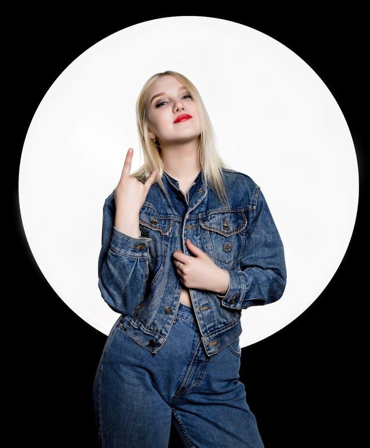 De jonge hooligan in jeans en een denimjasje toont verschillende tekens met haar vingers royalty-vrije stock afbeelding