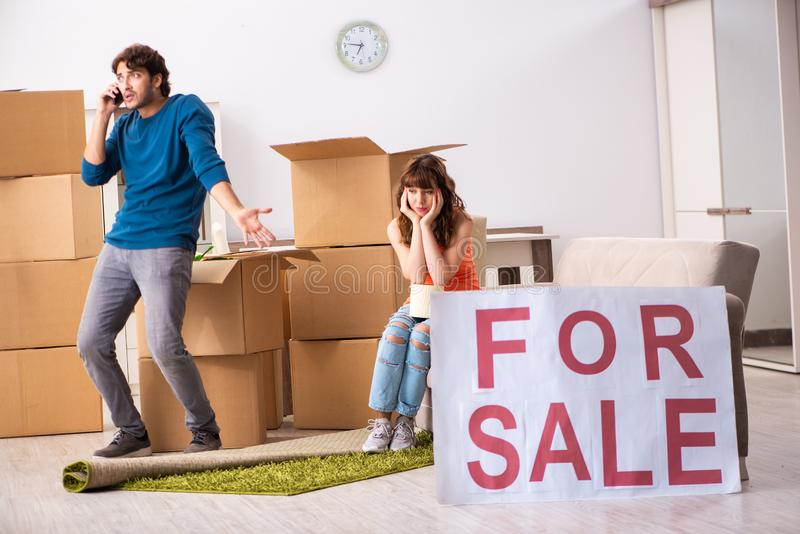 De jonge huis voor verkoop aanbieden en familie die zich uit bewegen stock foto's