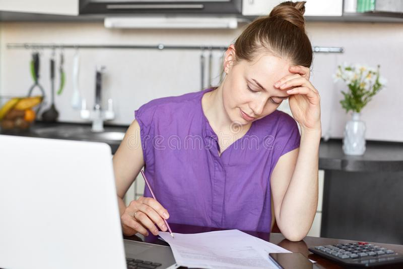 De jonge huisvrouw berekent familieuitgaven, moet loonsrekeningen voor huur en het gas, bekijkt documenten, werkt met laptop comp stock afbeelding