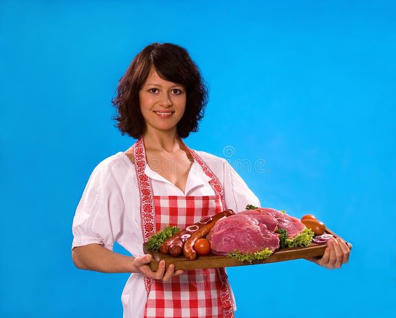 De jonge huisvrouw biedt vleeswaren aan royalty-vrije stock afbeeldingen