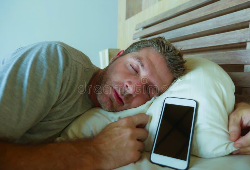 De jonge Internet-slaap die van de verslaafdenmens op bed mobiele telefoon in van hem houden dient smartphone en sociale media ex stock afbeelding