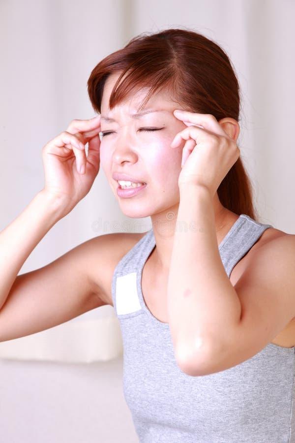 De jonge Japanse vrouw lijdt aan hoofdpijn royalty-vrije stock afbeelding