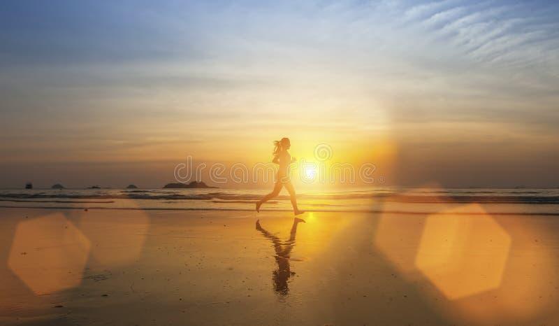 De jonge Jogging van het meisjessilhouet op overzees strand stock afbeeldingen