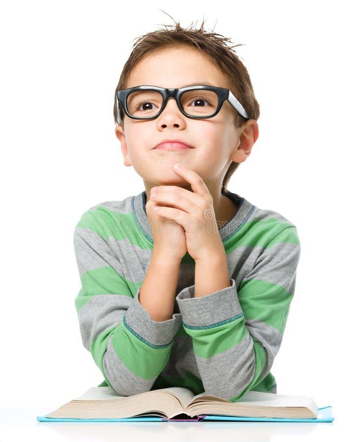 De jonge jongen dagdroomt terwijl het lezen van boek royalty-vrije stock foto's