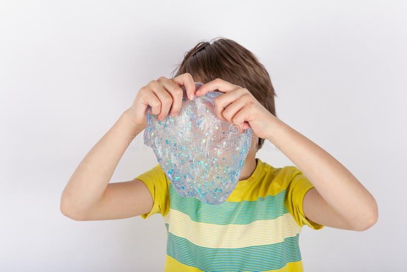 De jonge jongen die transparant houden schittert slijm voor zijn gezicht royalty-vrije stock foto