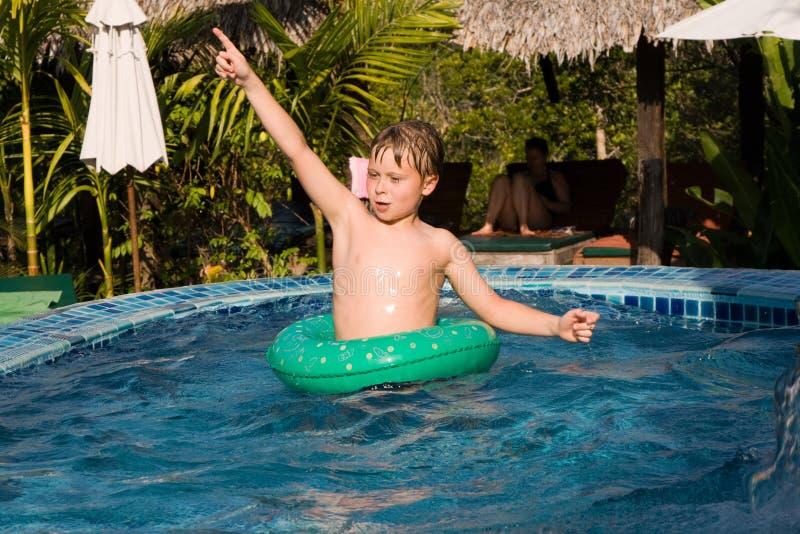 de jonge jongen in een floting band geniet van vers poolwater royalty-vrije stock foto's