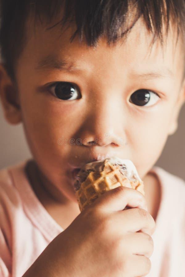 De jonge jongen eet het close-up van het roomijsgezicht stock afbeeldingen