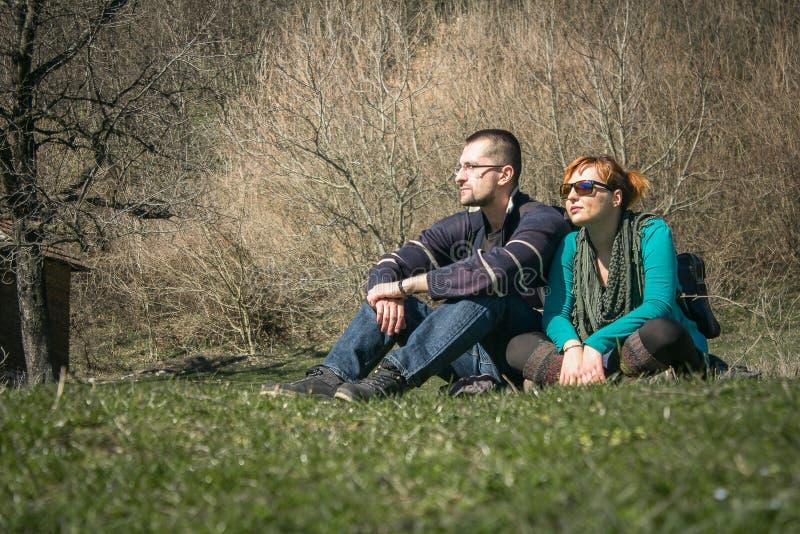 De jonge jongen en het meisje die op het gras in het park situeren en en genieten van stock foto's