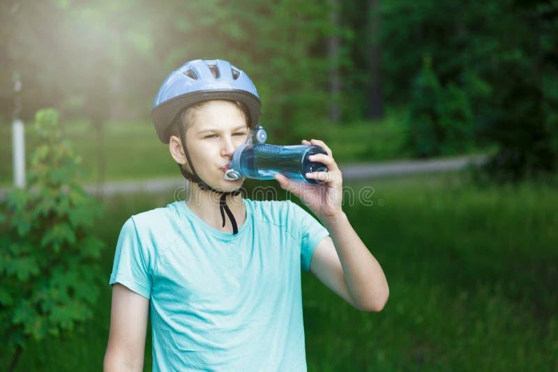 De jonge jongen in helm en groene t-shirtfietser drinkt water van fles in het park Glimlachende leuke Jongen op fiets in het bos royalty-vrije stock afbeelding