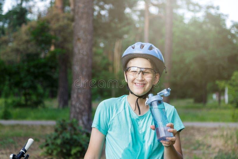 De jonge jongen in helm en groene t-shirtfietser drinkt water van fles in het park Glimlachende leuke Jongen op fiets in het bos stock afbeelding