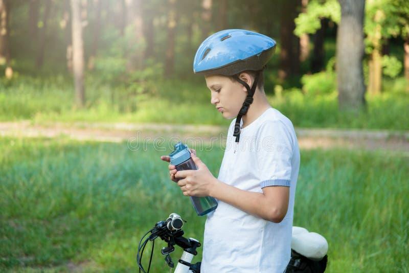 De jonge jongen in helm en witte t-shirtfietser drinkt water van fles in het park Glimlachende leuke Jongen op fiets in het bos stock foto