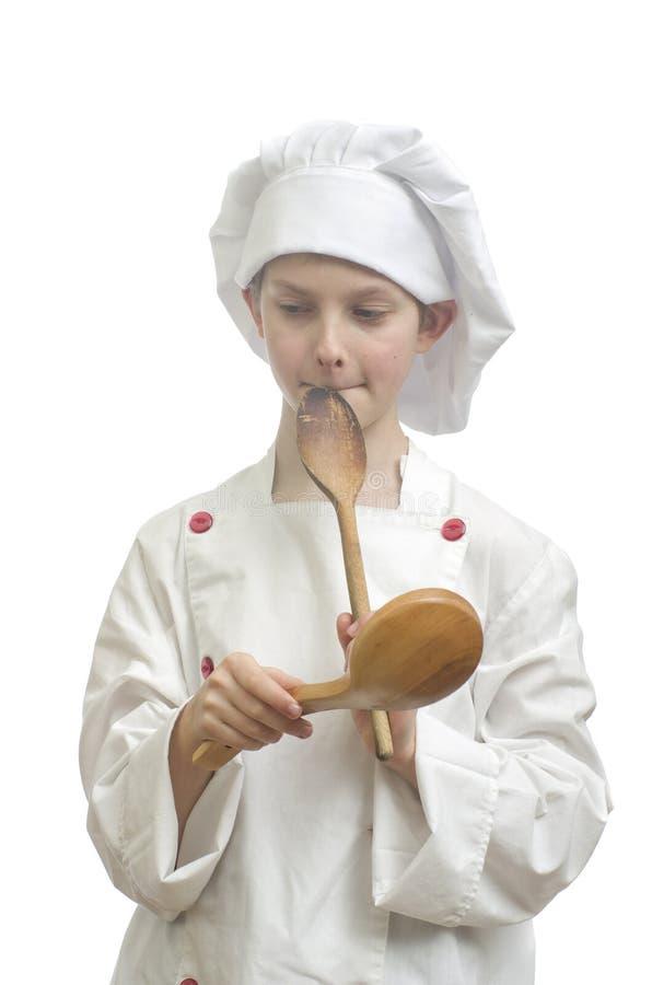 De jonge jongen kleedde zich als chef-kok met houten lepels op witte achtergrond stock afbeelding