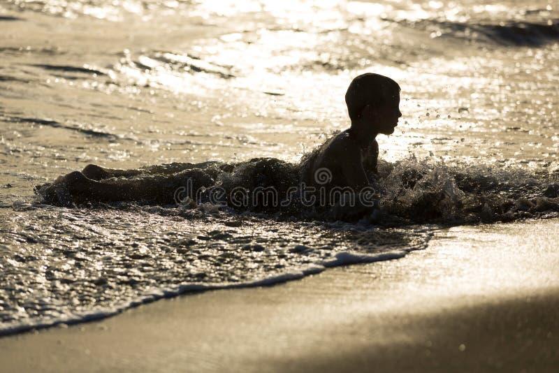 De jonge jongen legt in water bij het zandige strand, zonsondergang royalty-vrije stock foto's