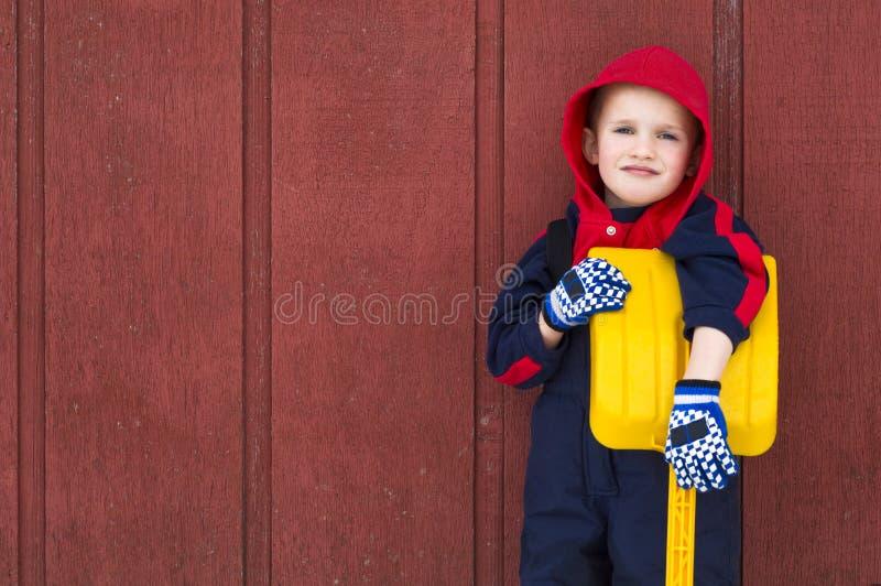 De jonge jongen leunt op zijn stuk speelgoed schop royalty-vrije stock foto's