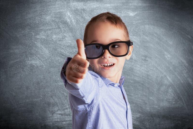 De jonge jongen met oogglazen voor schoolbord het tonen beduimelt omhoog Oogonderzoek, onderwijs en het leren concept stock foto