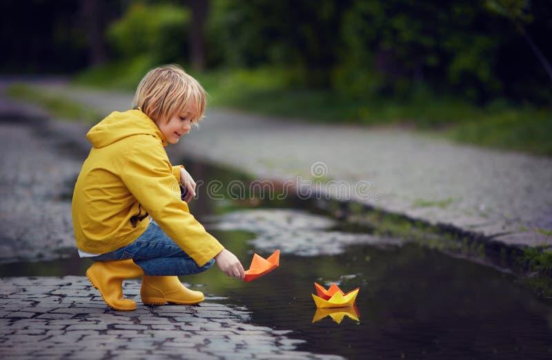De jonge jongen in regenlaarzen en laag zet document boten op het water, bij de lente regenachtige dag stock fotografie