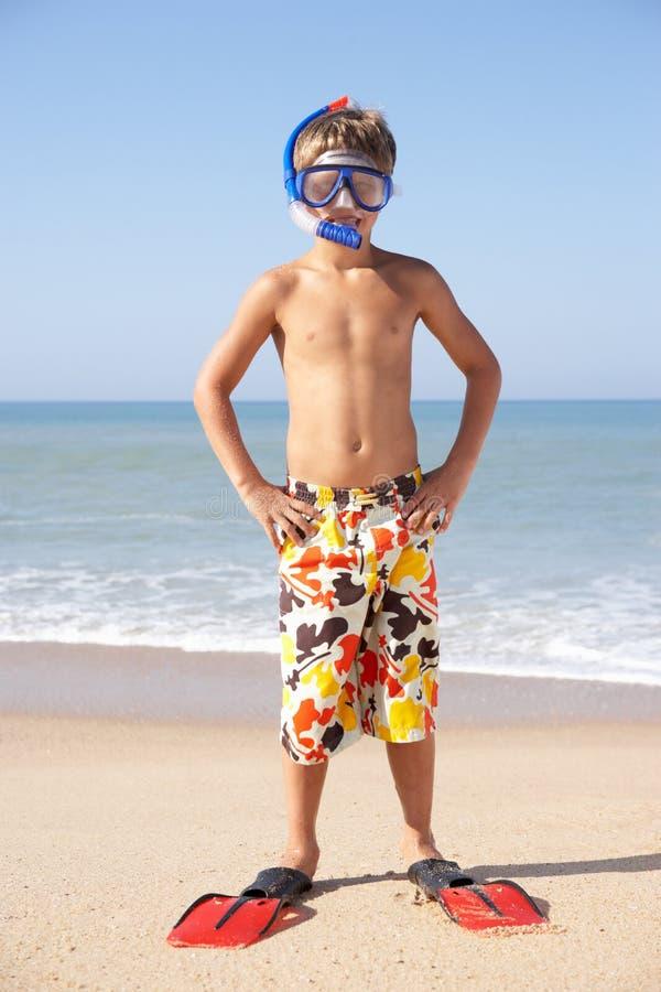 De jonge jongen stelt op strand stock foto
