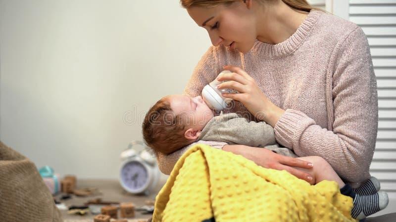 De jonge jongen van de dame voedende baby, fles met zuigelingsformule, die jong geitje zetten aan slaap stock foto's