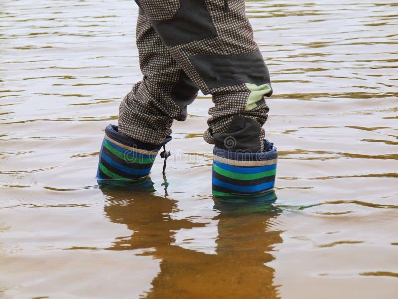 De jonge jongen wast rubberlaarzen in modderig water van vijver Vuil zand stock fotografie