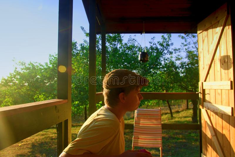De jonge jongen zit op een veranda en eet verse appelen Dromerig en romantisch beeld De zomer en gelukkige kinderjaren stock foto