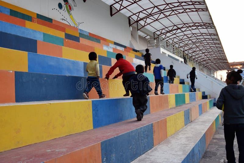 De jonge jongens beklimmen op weg naar huis over de stadionstappen van een na-schoolprogramma in Cuzco, Peru stock foto's