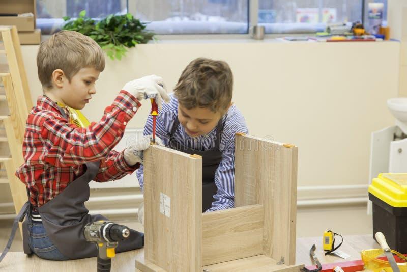 De jonge jongens construeren houten kruk royalty-vrije stock afbeeldingen
