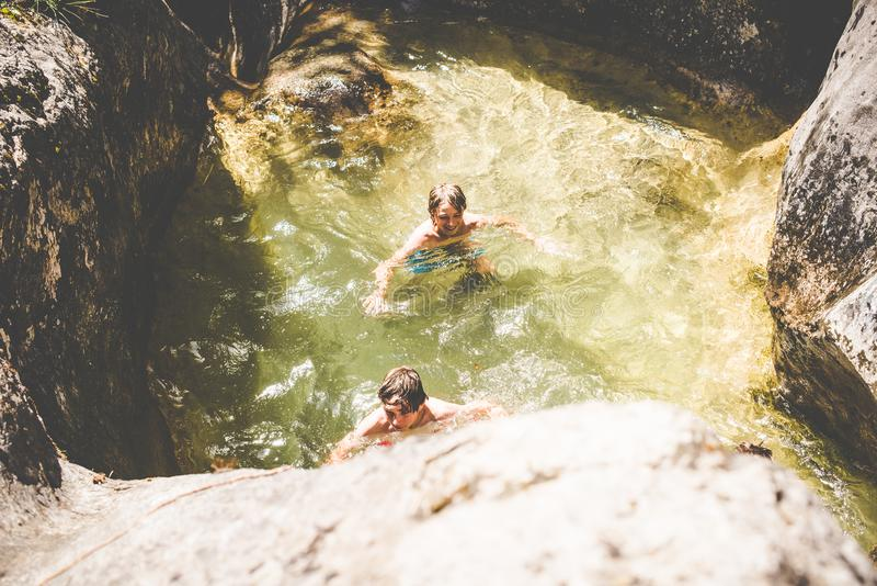 De jonge jongens hebben pret bij de kleine rivier royalty-vrije stock afbeeldingen
