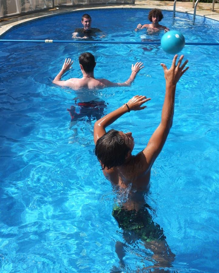 De jonge jongens spelen volleyball in pool royalty-vrije stock afbeelding