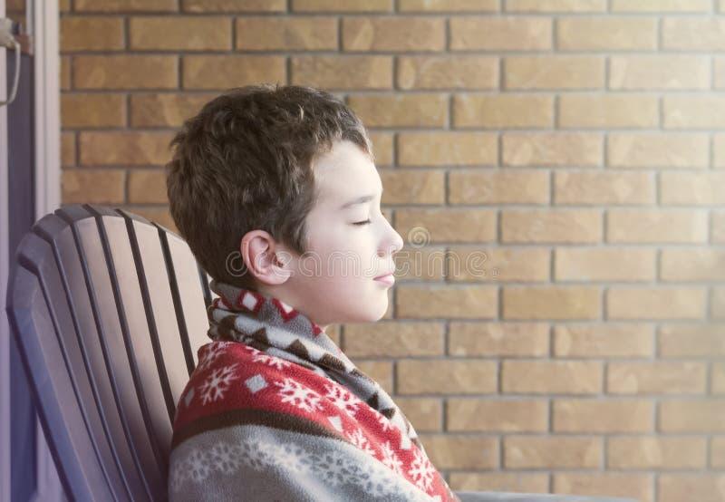 De jonge jongenszitting op gesloten portiekogen, verpakt in deken geniet van royalty-vrije stock afbeelding