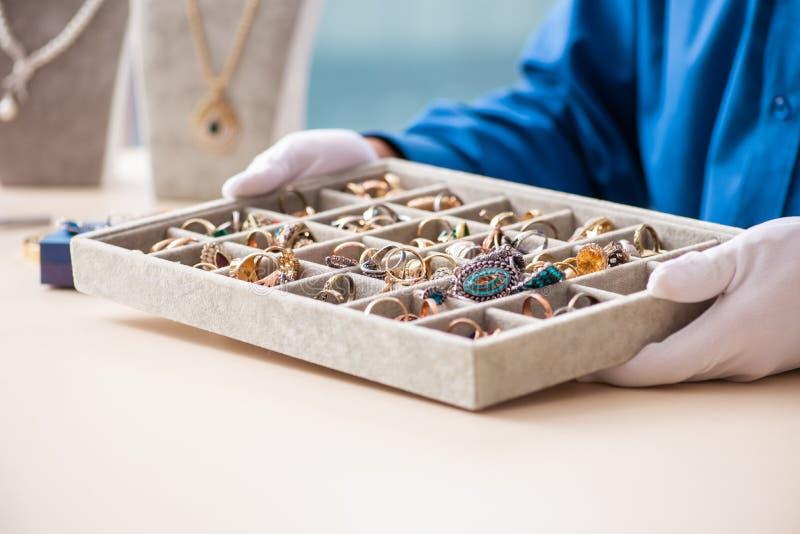De jonge juwelier die in zijn workshop werken stock foto
