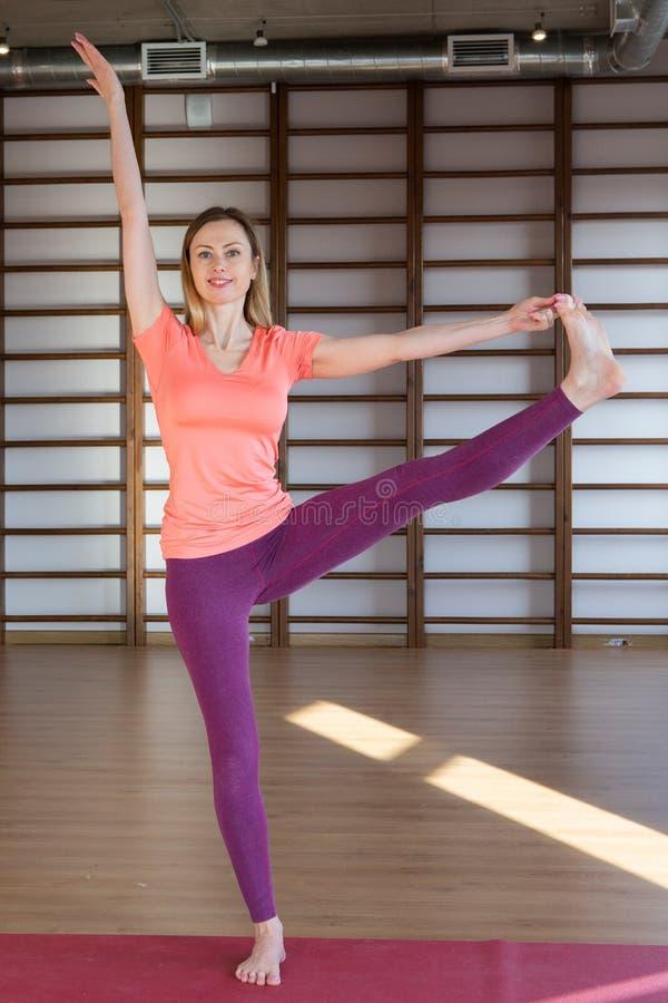 De jonge kalme mooie vrouw die witte sportkleding dragen die, doend yoga of pilates oefent uitwerken uit Volledige lengte royalty-vrije stock foto