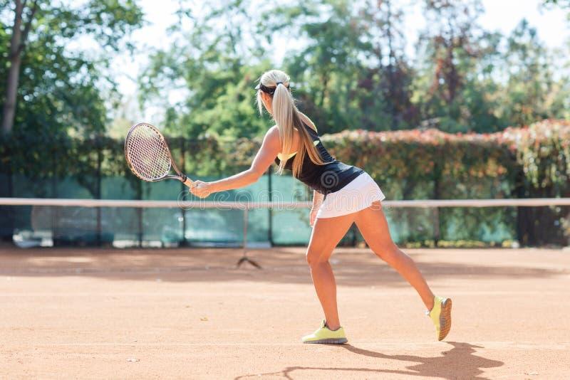De jonge Kaukasische blondevrouw speelt tennis openlucht Mening van rug De speler van het tennis in actie Horizontaal beeld stock foto