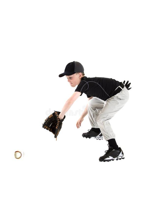 De jonge Kaukasische jongen die een honkbal met mitt vangen backhanded stock fotografie