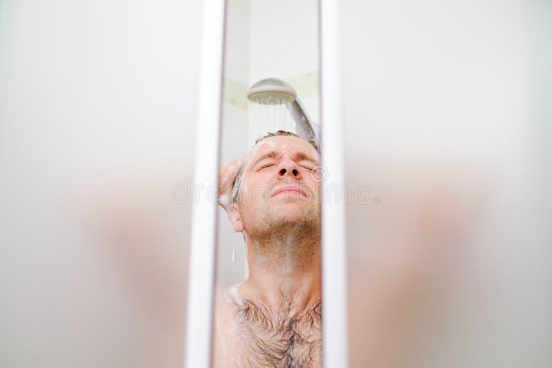 De jonge Kaukasische mens die zijn haar wassen, die een douche met schuim op zijn hoofd nemen houdt vingers in haar stock afbeelding