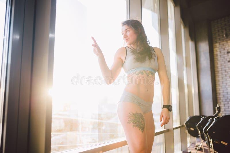 De jonge Kaukasische sportieve vrouw met krullend lang haar stelt in sportkleding dichtbij een panorman venster in een geschikthe stock foto's
