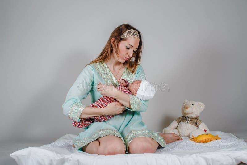 De jonge Kaukasische vrouw kalmeert een pasgeboren baby royalty-vrije stock afbeeldingen